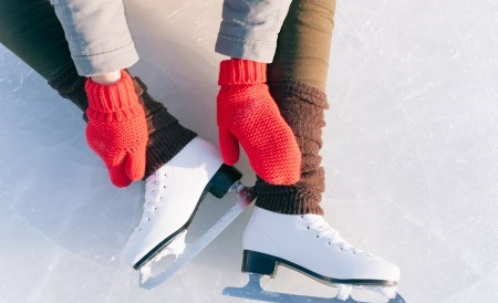 person sitting on ice in skates wearing red gloves