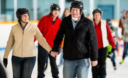 Elderly couple holding hands ice skating